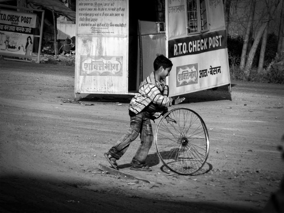 boy rolling a bicycle tire