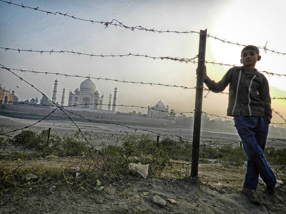 boy leans on barbed wire fence with Taj Mahal in background