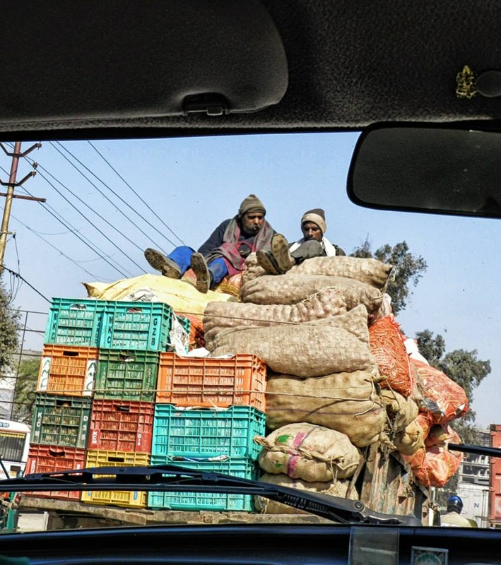 men riding on top of tall pile of goods on back of truck