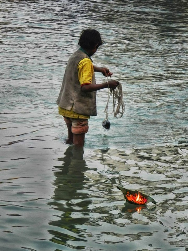boy fishes for coins in Ganges with magnet on rope