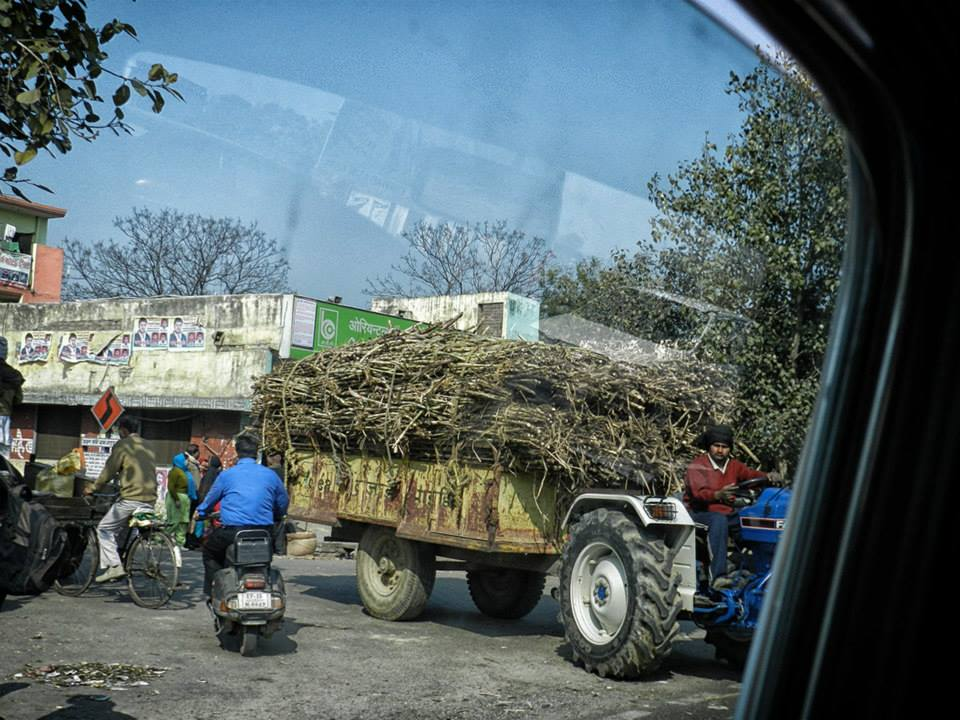 tractor pulling cart loaded with sugarcane