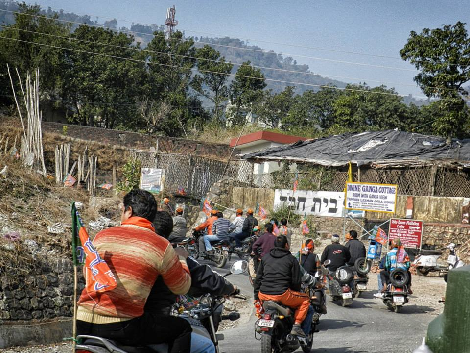 Men ride motorcycles and carry flags for election rally in Rishikesh, India