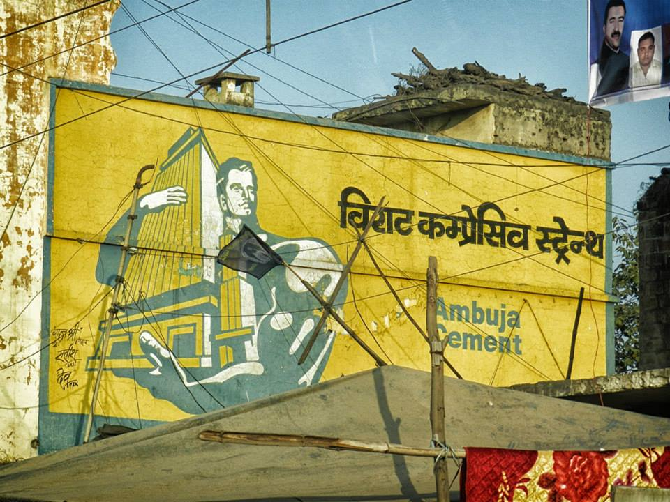 Advertisement for Ambuja Cement - man holding a building painted on a wall