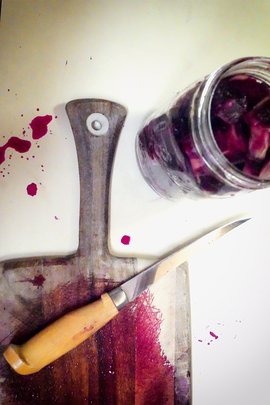 Cutting board with knife and red spatters next to jar of red cut up flesh