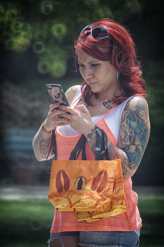woman with red hair looks at phone