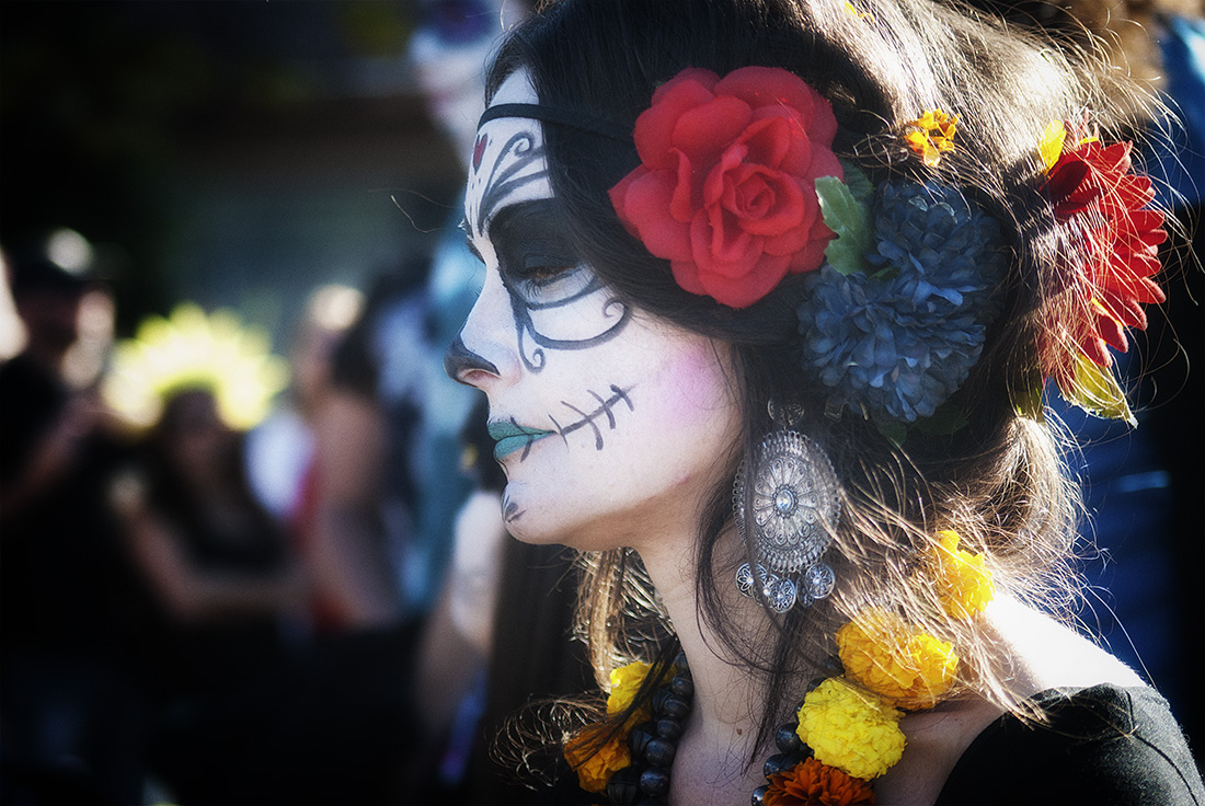 Woman with calavera makeup and flowers in hair