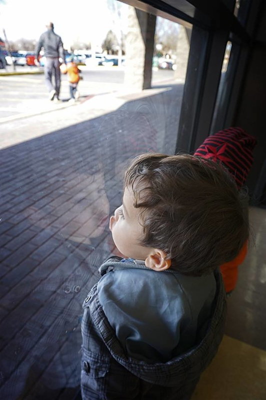 child makes face in window, with reflection