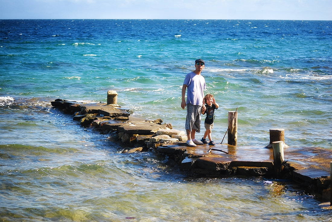 father and son walk out on concrete dock roatan honduras