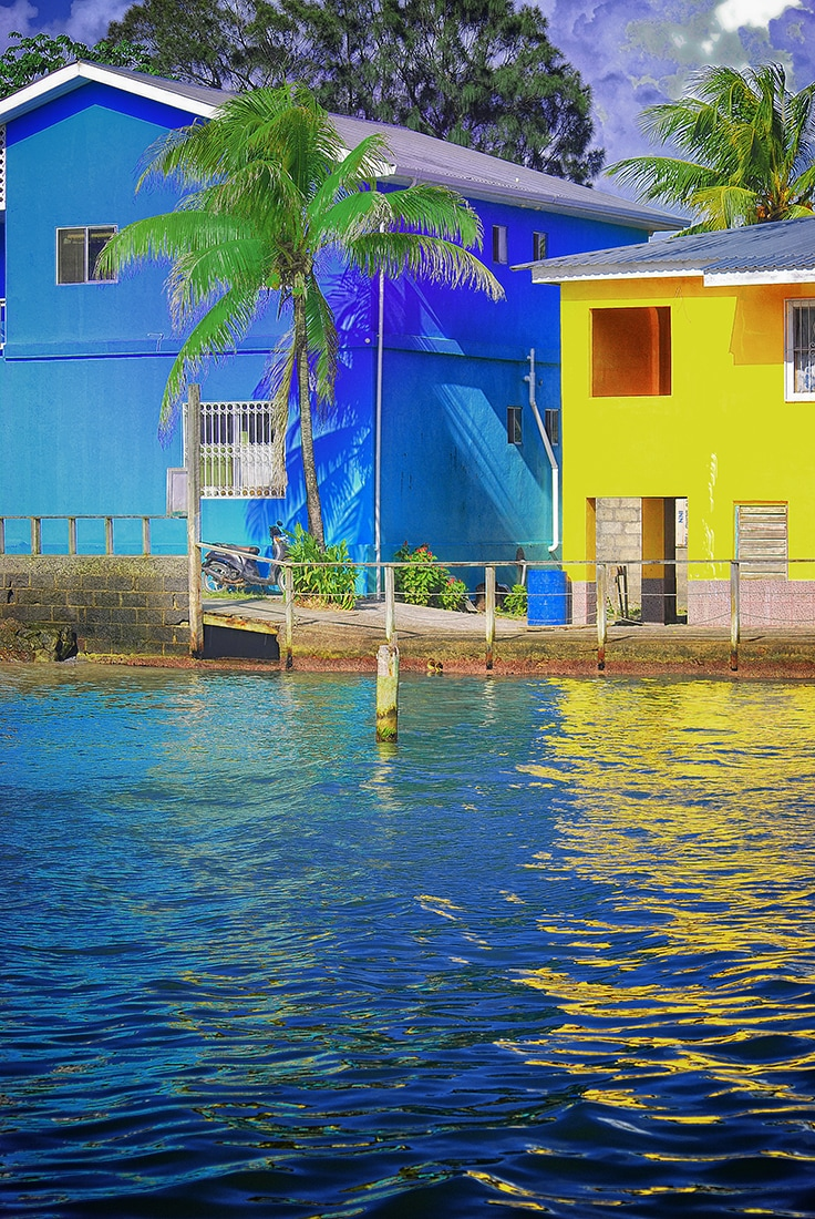 blue and yellow buildings reflect on water roatan honduras