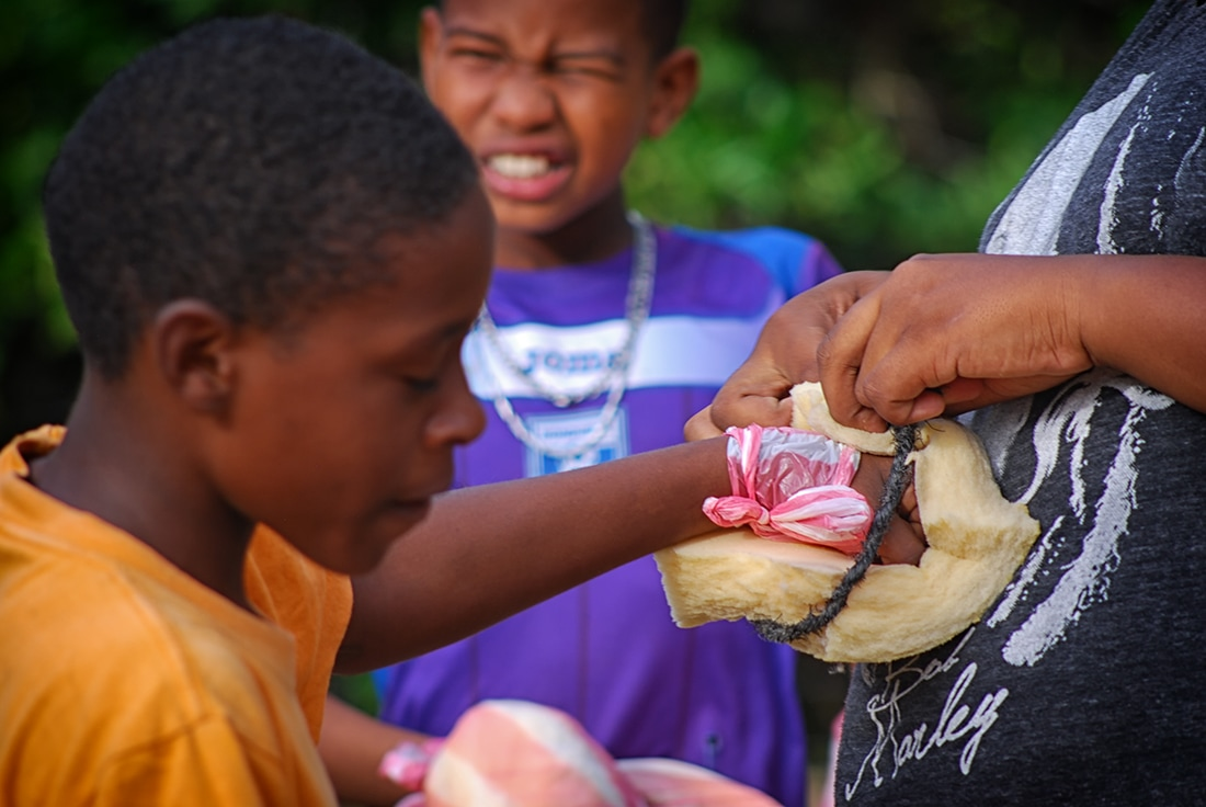 kids put on boxing gloves made of foam, cord, and plastic bags roatan honduras