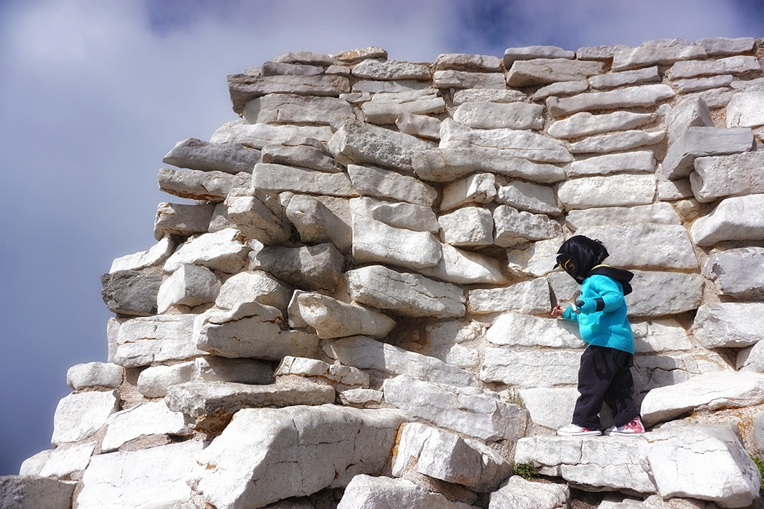 child climbs on stone wall