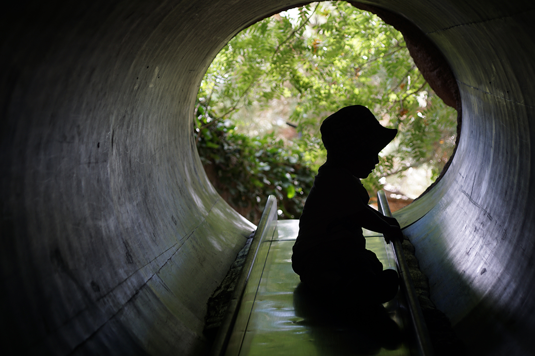 child silhouette in tube slide