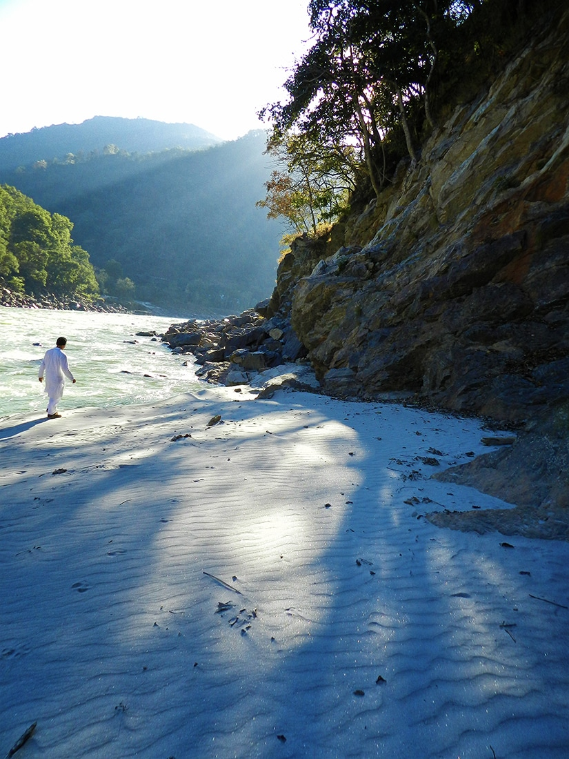 man walks on white sand beach of ganges near rishikesh, India