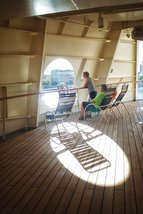 couple on cruise ship with circular window and deck chair shadow