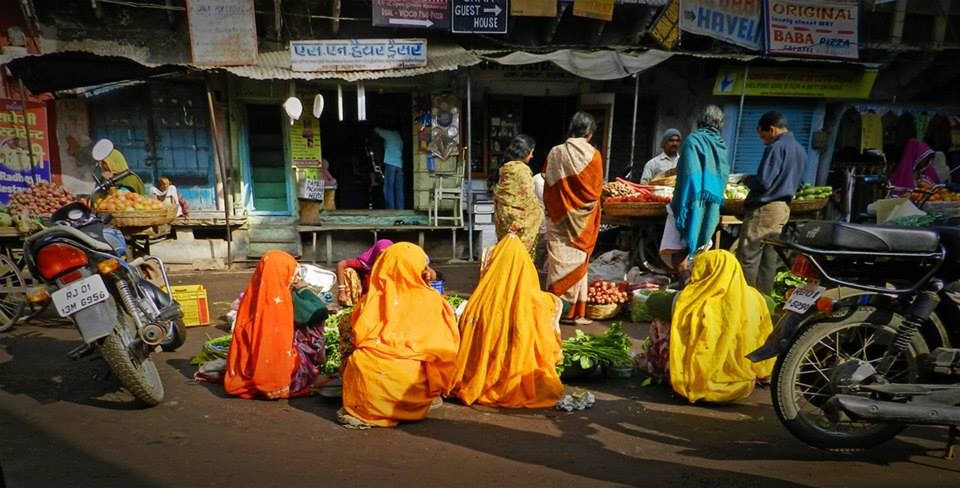 group of women sell goods in marketplace