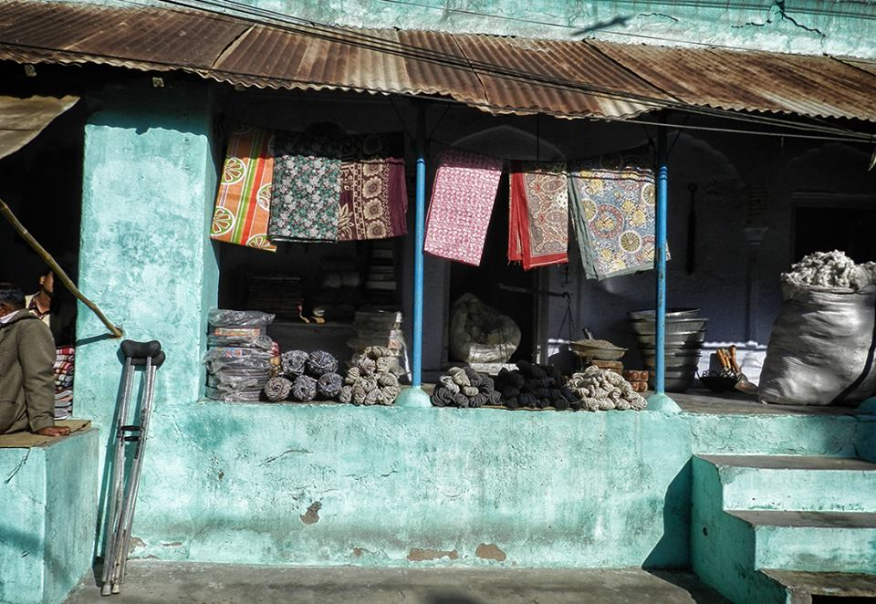 turquoise open storefront with textiles hanging and bags of yarn