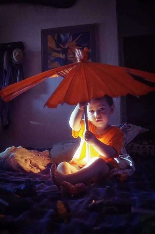 boy holds paper umbrella