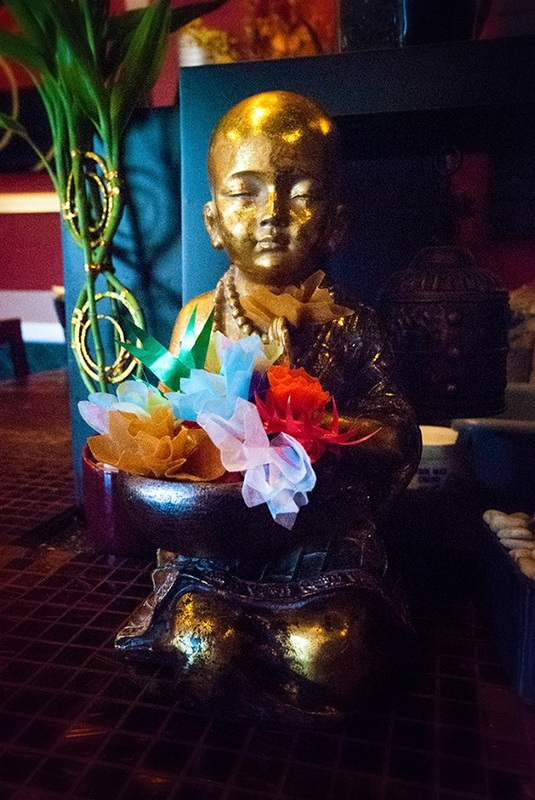Buddhist boy statue with flowers