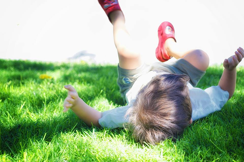 child rolls in grass
