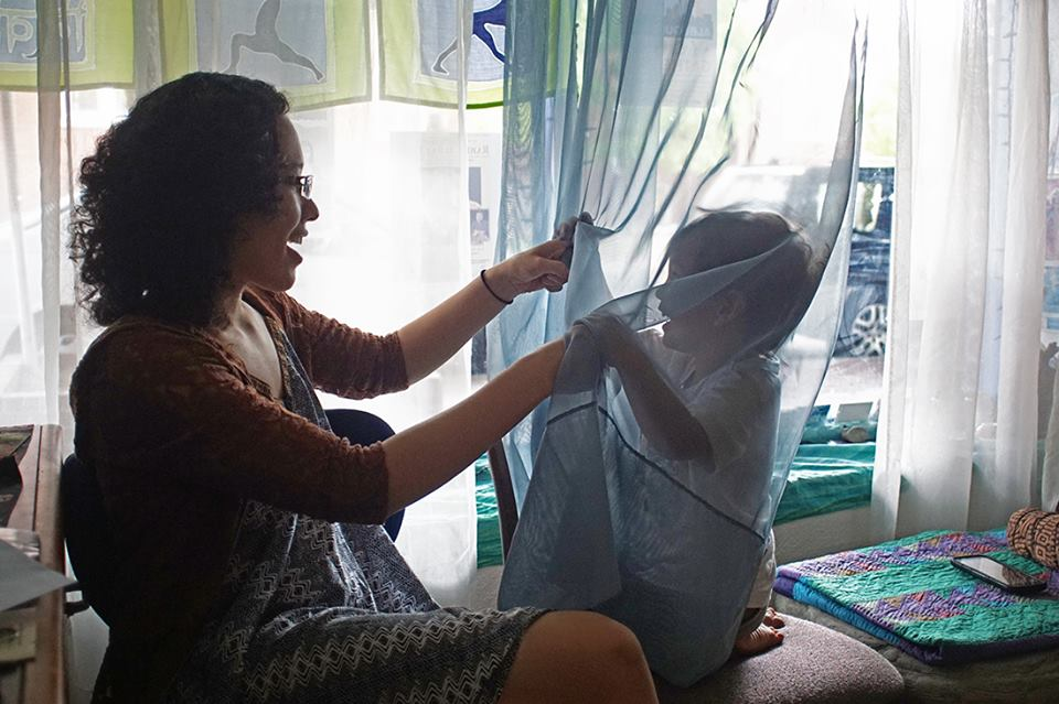 woman plays with child in curtains