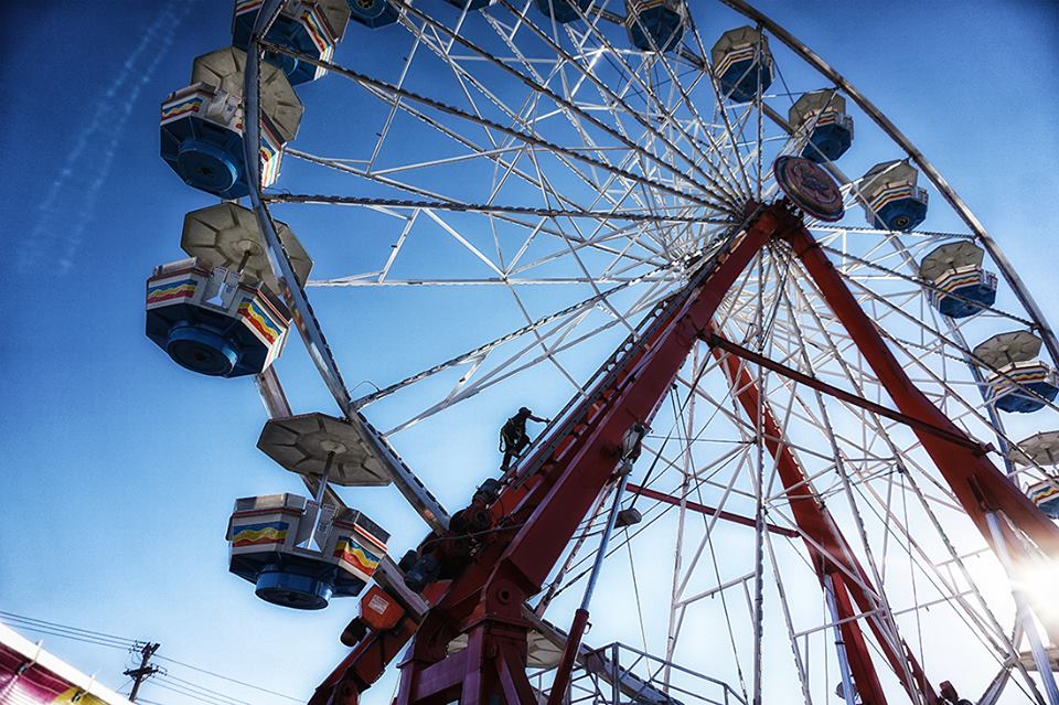 worker climbs to center of large ferris wheel