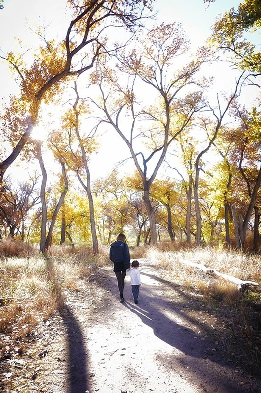 woman and boy walk in golden cottonwoods