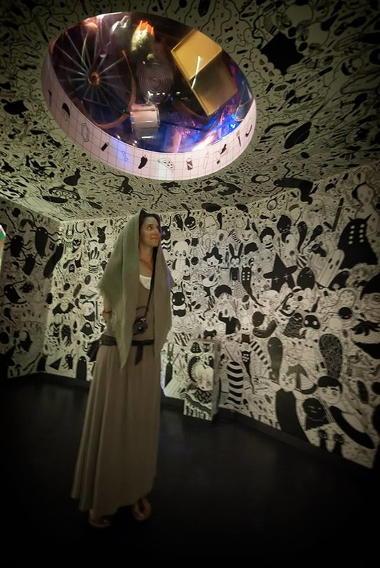 woman stands in black and white cartoon room at Meow Wolf