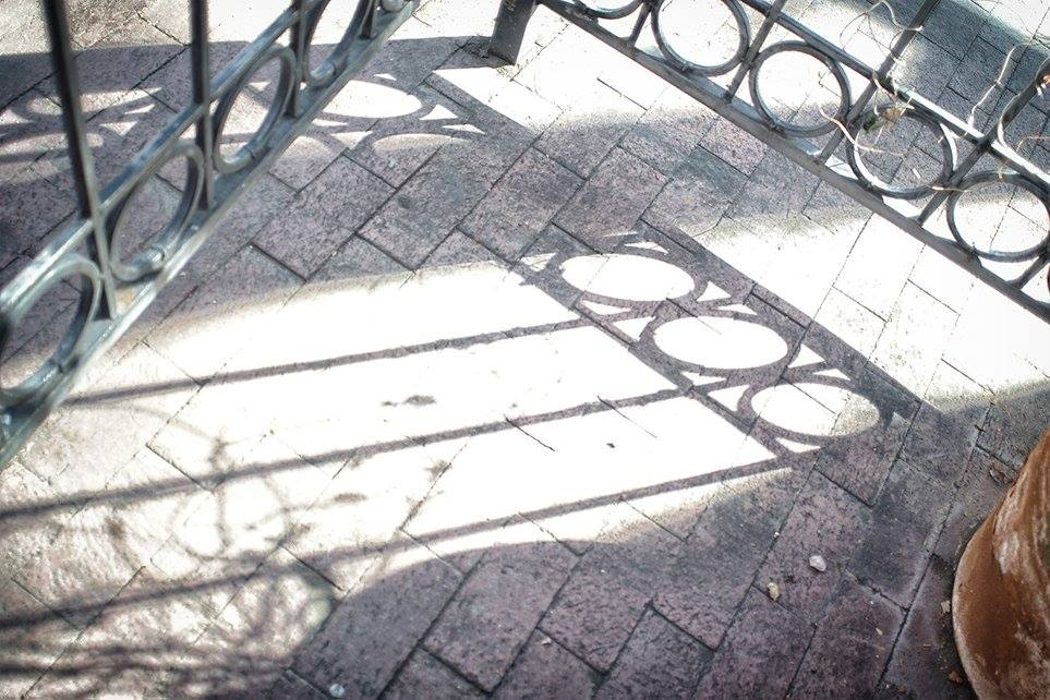 shadows of wrought iron fence and gate