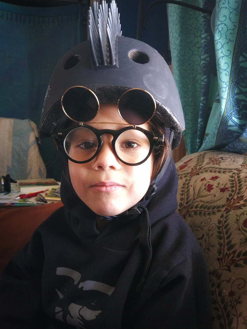 boy wears mohawk bike helmet with flip up glasses