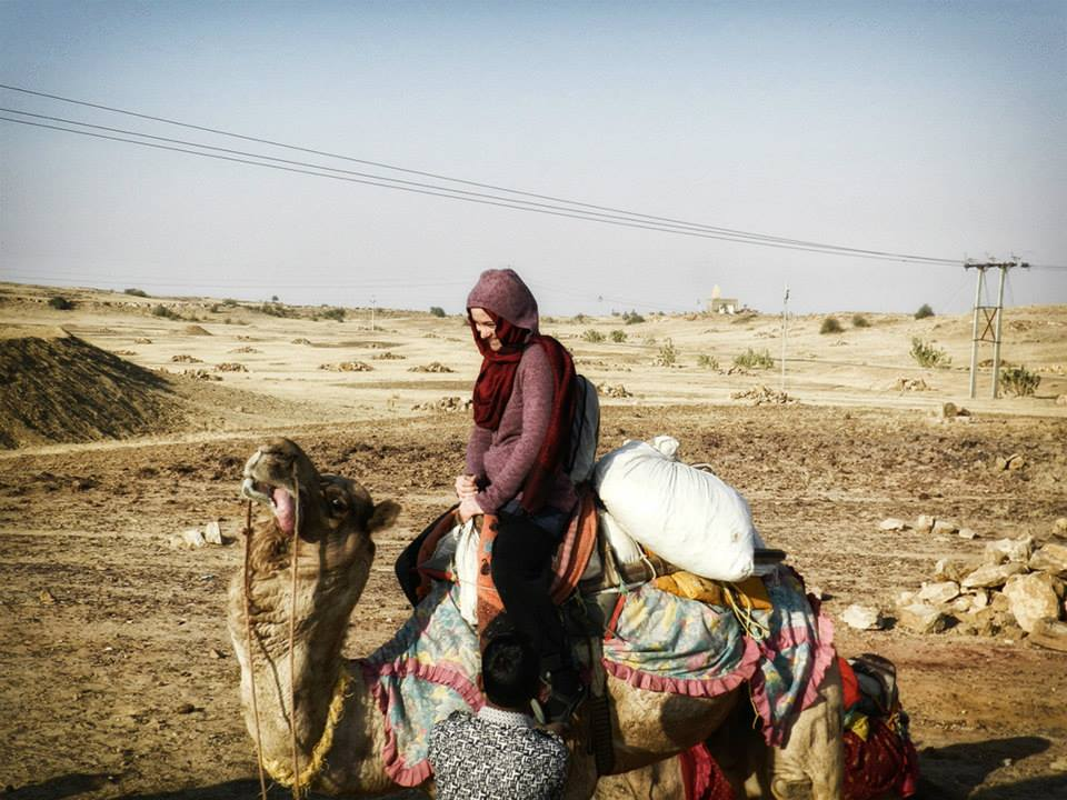 woman sits on camel