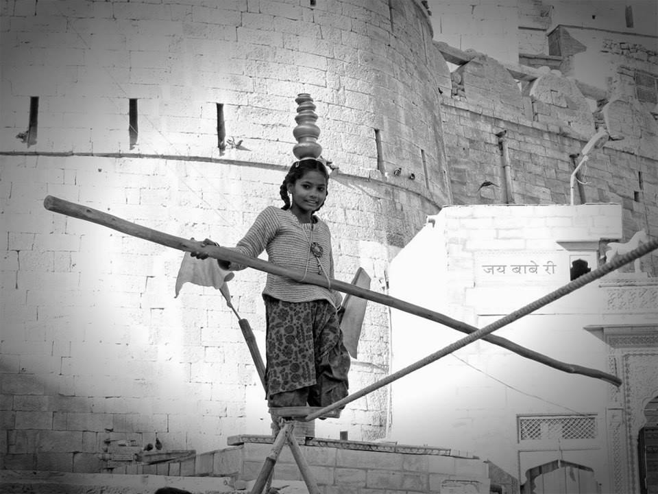 girl balances pots on head while tightrope walking