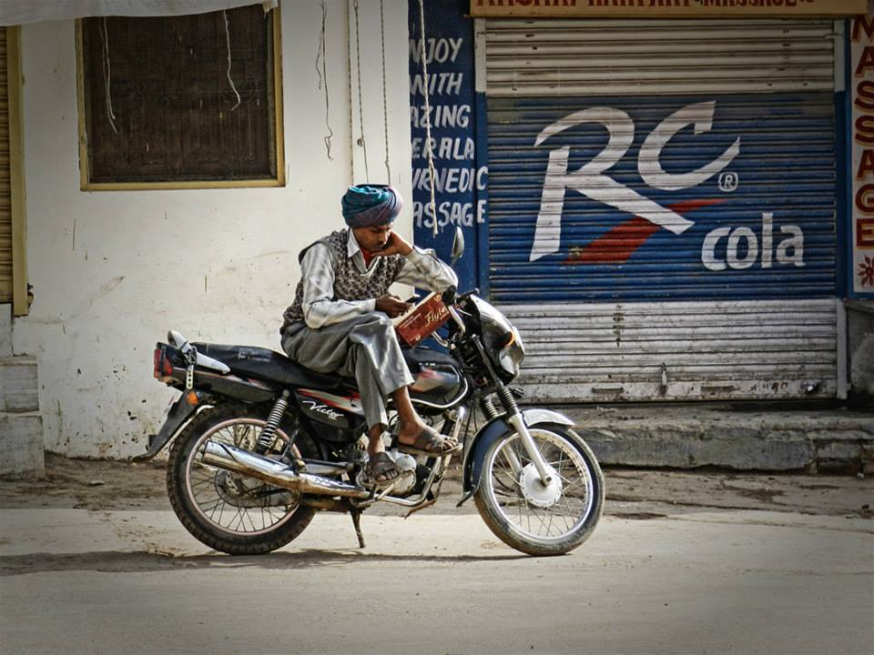 man sits on motorcycle reading in front of large rc cola advertisement
