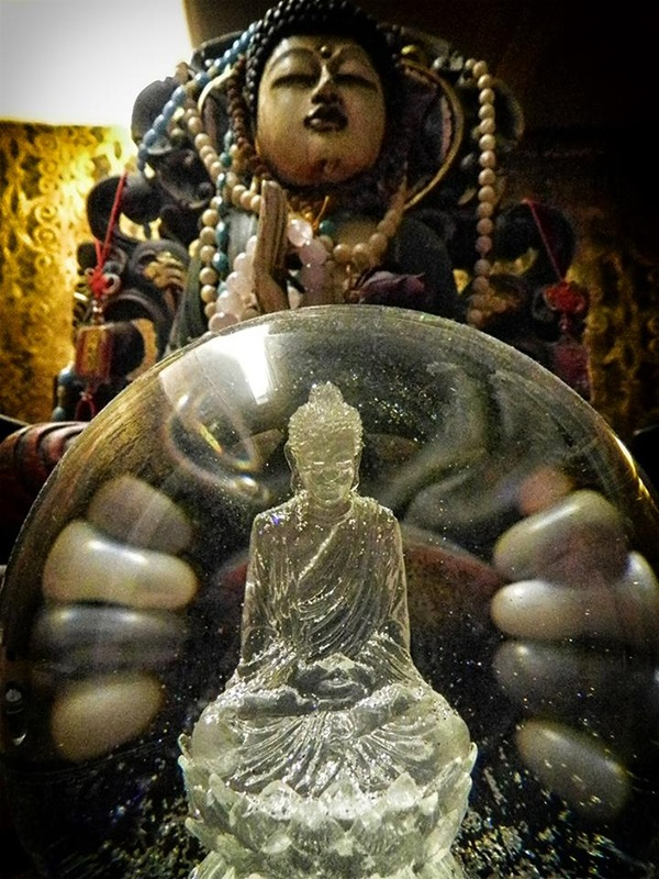 Buddha statue with bead garlands and Buddha snowglobe
