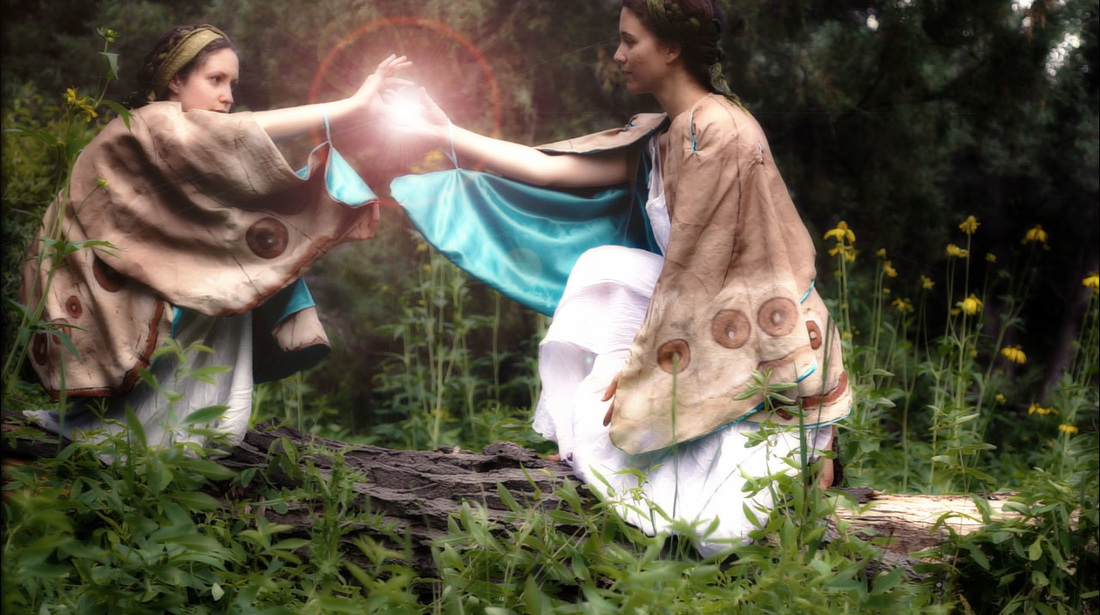 women in butterfly capes with laser flare