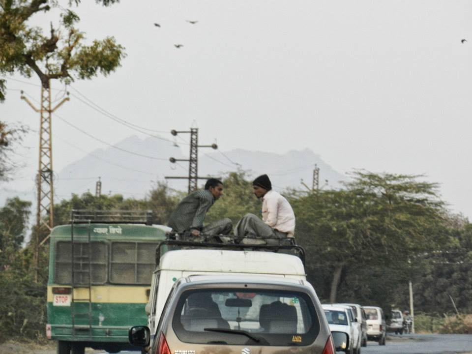men sitting on top of truck driving on road
