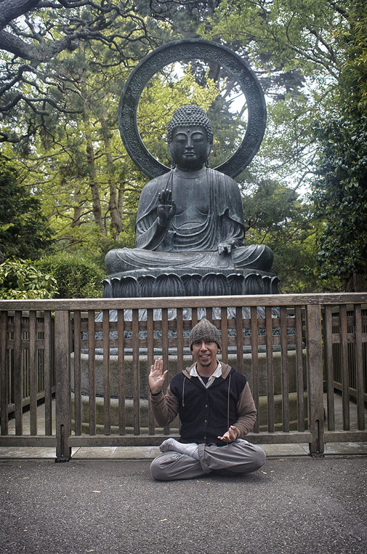 man in lotus position by Buddha statue Japanese Tea Garden