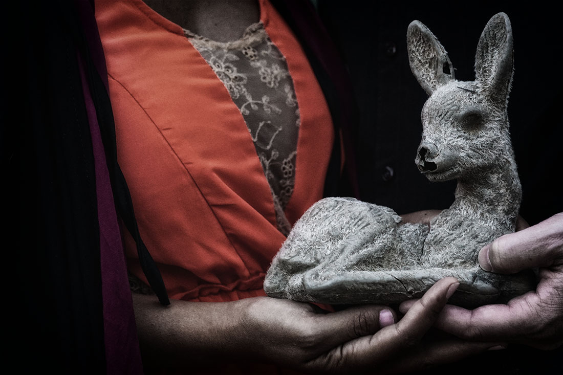 couple holding creepy fawn statue