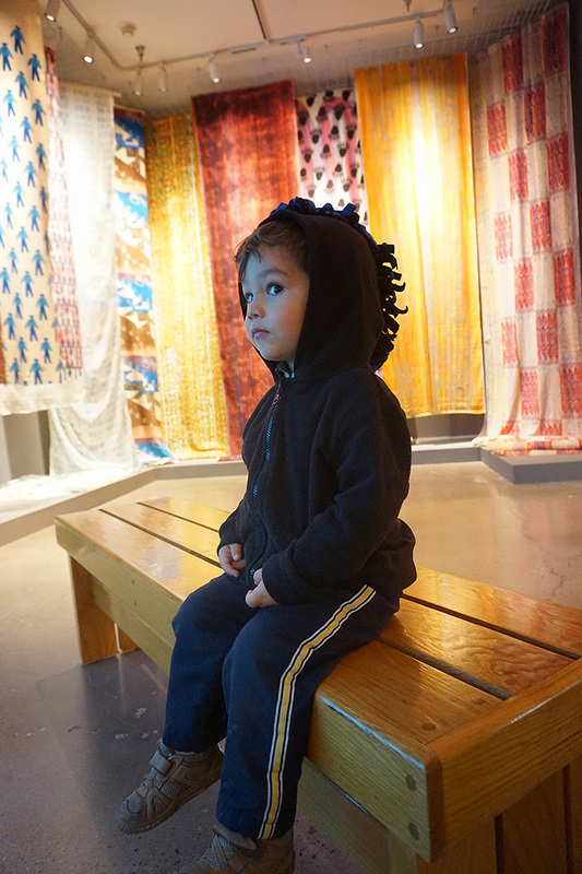 child looks at printed cloth hanging in museum