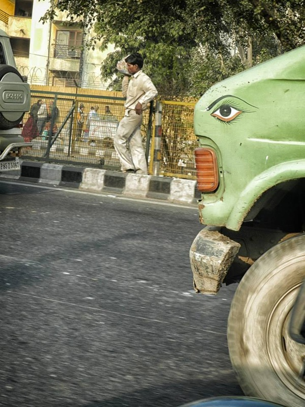 man walking on side of street with a green truck painted with eye