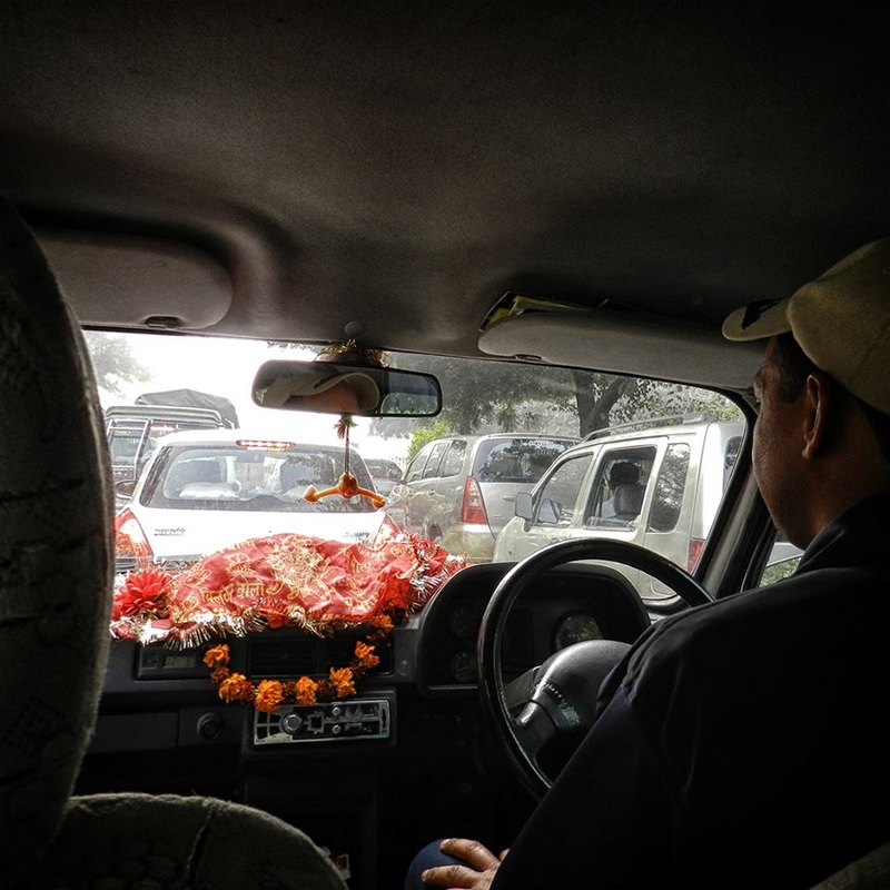 from inside the car - driver and traffic, hanging Hanuman and flowers