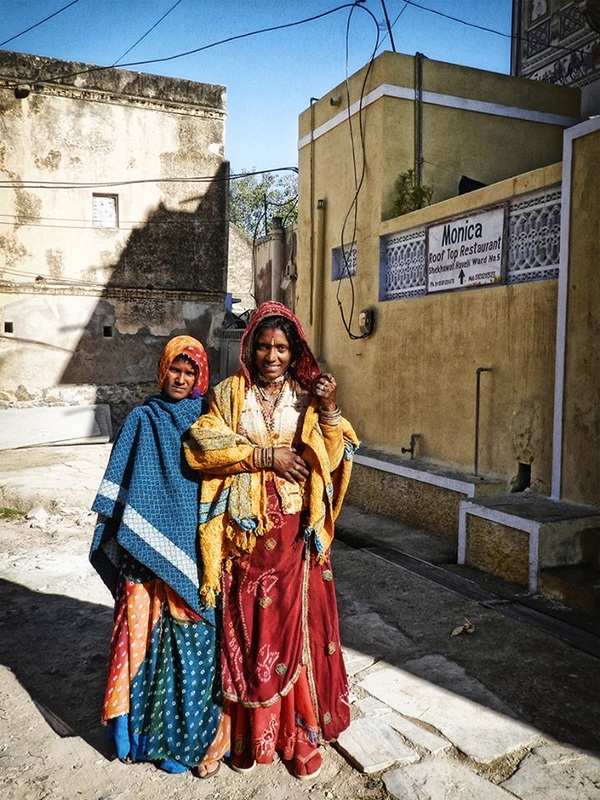 women pose for photo in exchange for rupees