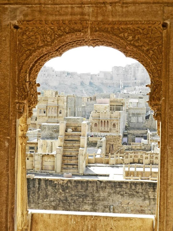 view of buildings from the archway of a carved window