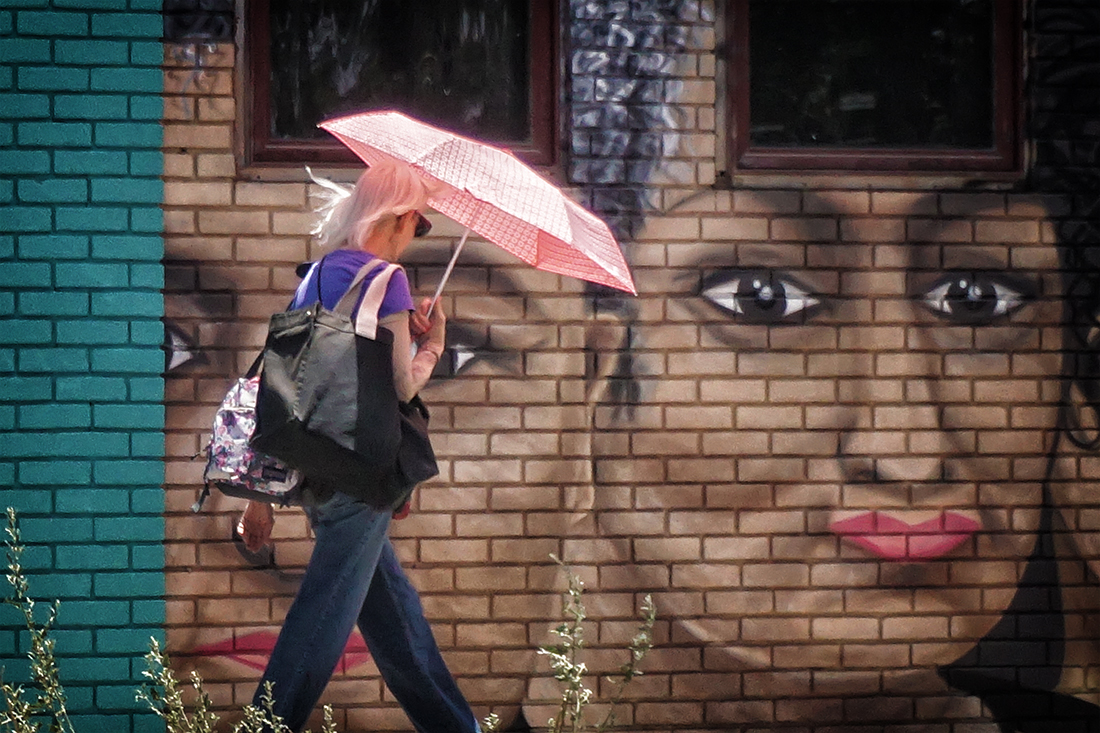 woman with pink umbrella walks in front of mural