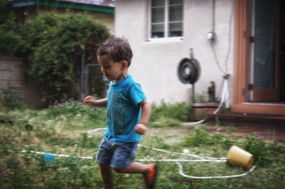 child runs in rain