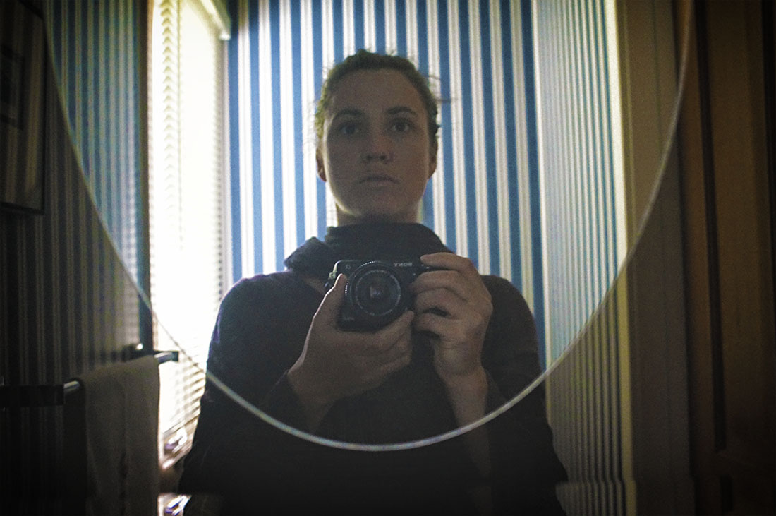 woman in mirror with striped wallpaper