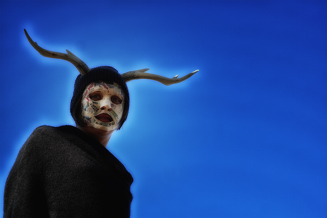 woman with antlers and mask against dark blue sky