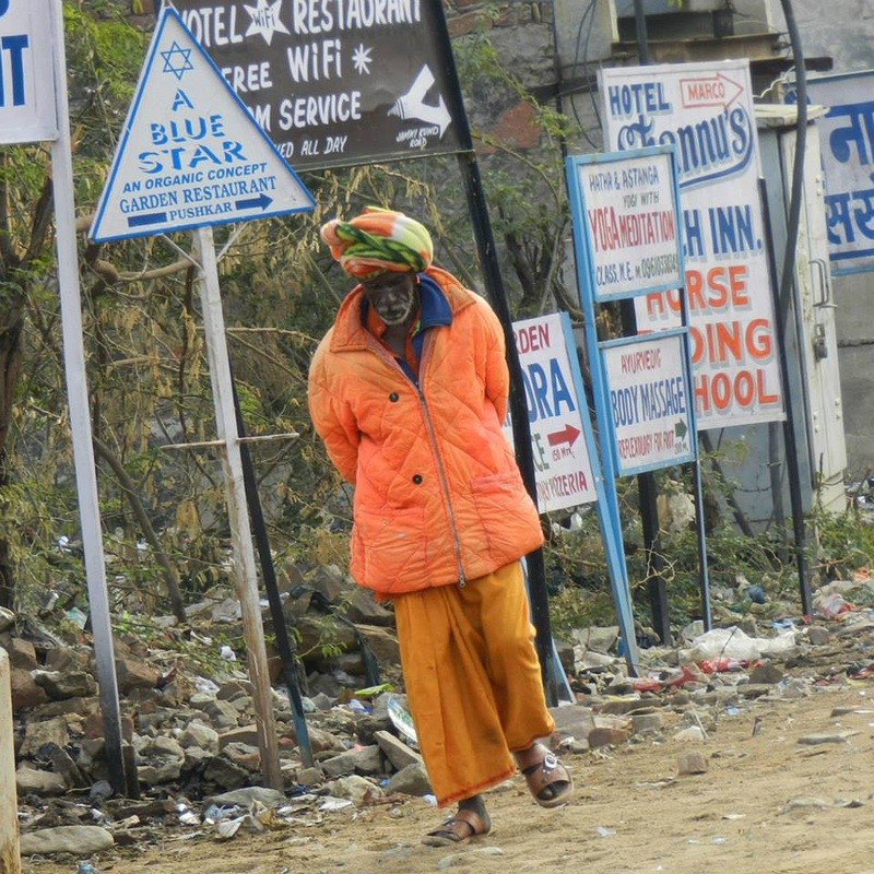 man dressed in orange walks along road side by trash and signs
