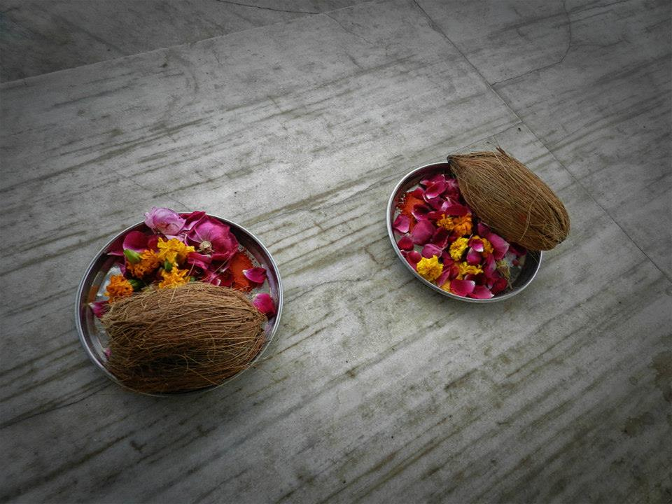 prayer offerings - metal dishes with coconuts and flowers to put in water at ghats