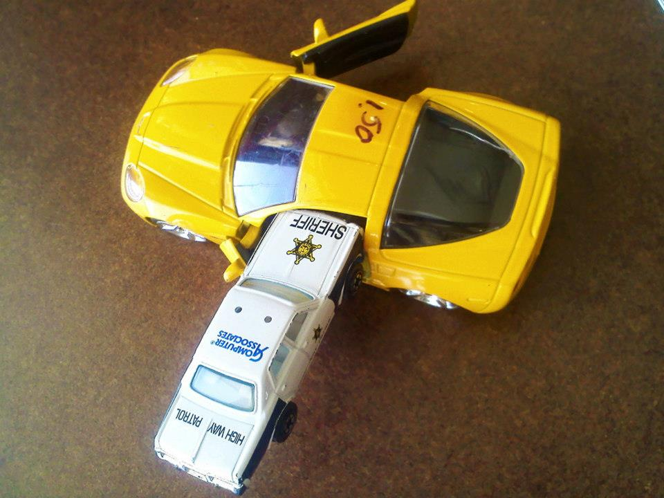 toy corvette with toy sheriff car stuck in door