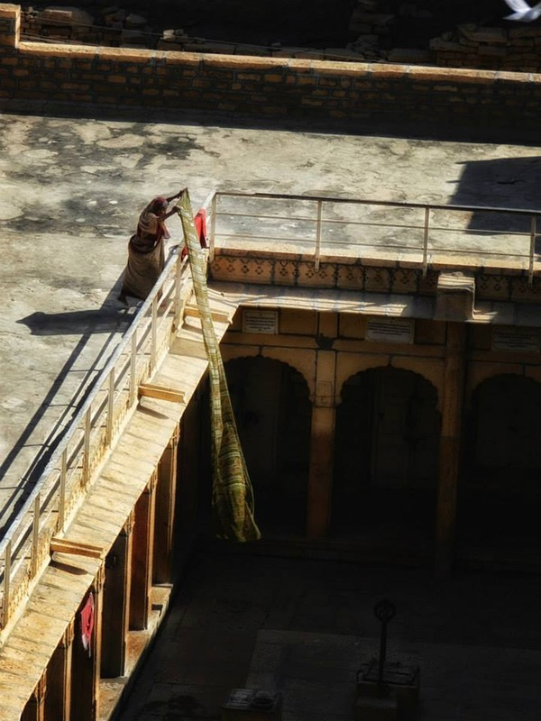 woman hangs sari to dry over balcony